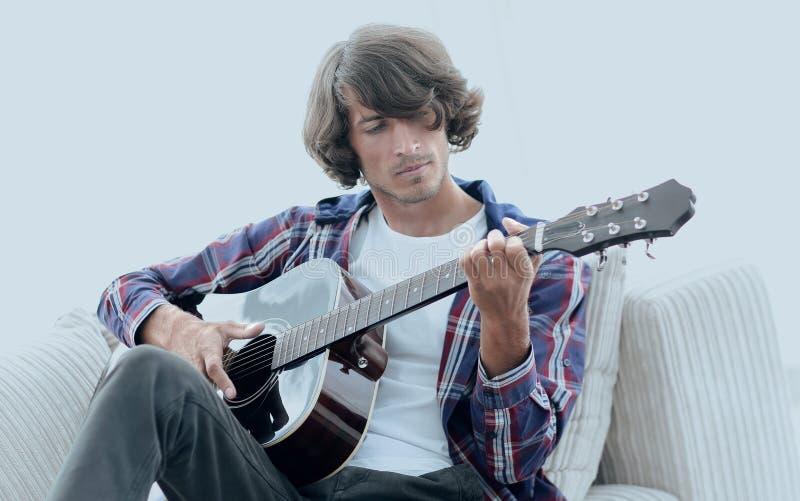 Όμορφο παιχνίδι ατόμων στην κιθάρα στον καναπέ στο σπίτι στοκ εικόνες