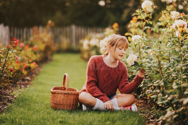 Όμορφο παιχνίδι κοριτσιών παιδάκι έξω στον κήπο λουλουδιών στοκ φωτογραφία