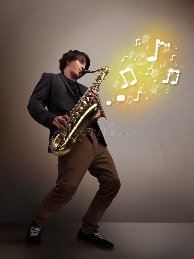 Όμορφο παιχνίδι μουσικών στο saxophone με τις μουσικές νότες στοκ φωτογραφία