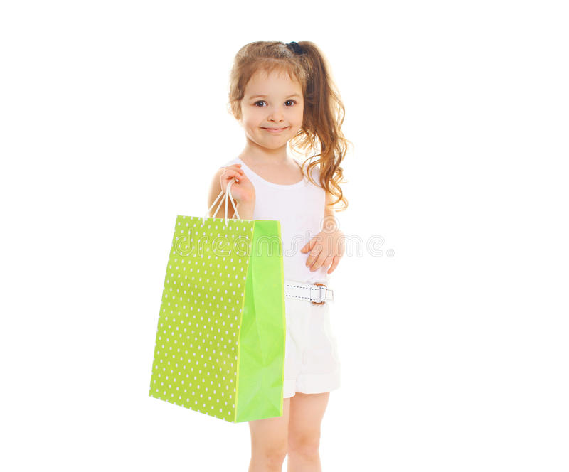 Όμορφο παιδί μικρών κοριτσιών με την τσάντα εγγράφου αγορών στο λευκό στοκ φωτογραφία με δικαίωμα ελεύθερης χρήσης
