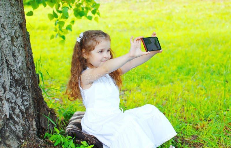 Όμορφο παιδί μικρών κοριτσιών που κάνει την αυτοπροσωπογραφία στο smartphone στοκ φωτογραφία