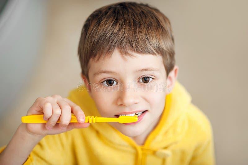 Όμορφο παιδί που προετοιμάζεται να βουρτσίσει τα δόντια τους που φορούν τα κίτρινα μπουρνούζια closeup στοκ εικόνα με δικαίωμα ελεύθερης χρήσης