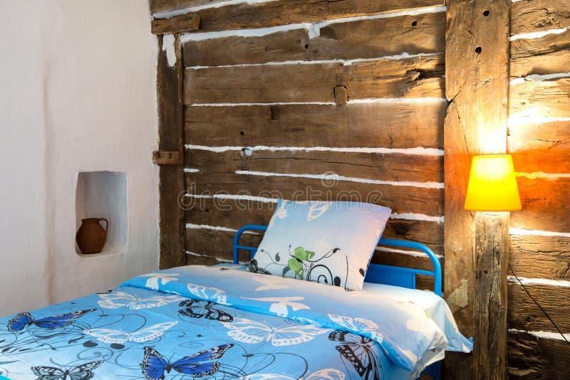Όμορφο παλαιό εκλεκτής ποιότητας εξοχικό σπίτι - εσωτερικό κρεβατοκάμαρων με το ξύλινο ανώτατο όριο ακτίνων και τα μπλε duvets κα στοκ εικόνες