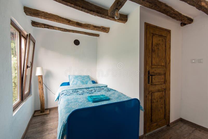 Όμορφο παλαιό εκλεκτής ποιότητας εξοχικό σπίτι - εσωτερικό κρεβατοκάμαρων με το ξύλινο ανώτατο όριο ακτίνων και τα μπλε duvets κα στοκ εικόνα