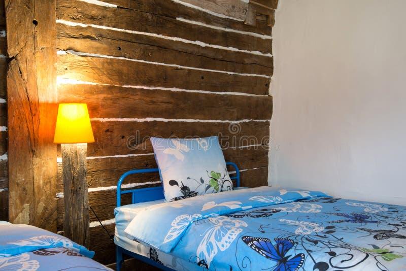 Όμορφο παλαιό εκλεκτής ποιότητας εξοχικό σπίτι - εσωτερικό κρεβατοκάμαρων με το ξύλινο ανώτατο όριο ακτίνων και τα μπλε duvets κα στοκ φωτογραφία