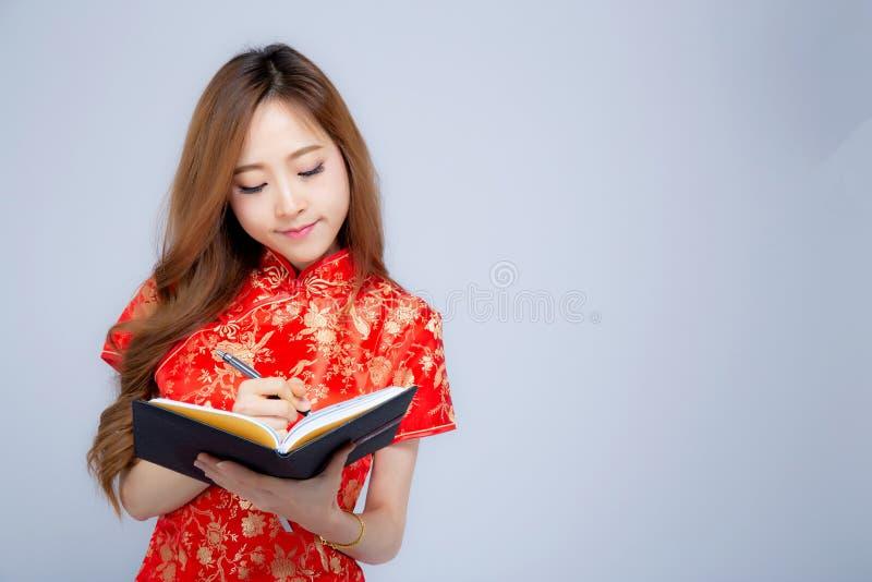 Όμορφο πορτρέτου νέο ασιατικό γυναικών σημειωματάριο γραψίματος cheongsam ένδυσης κόκκινο που απομονώνεται στο άσπρο υπόβαθρο στοκ φωτογραφία με δικαίωμα ελεύθερης χρήσης