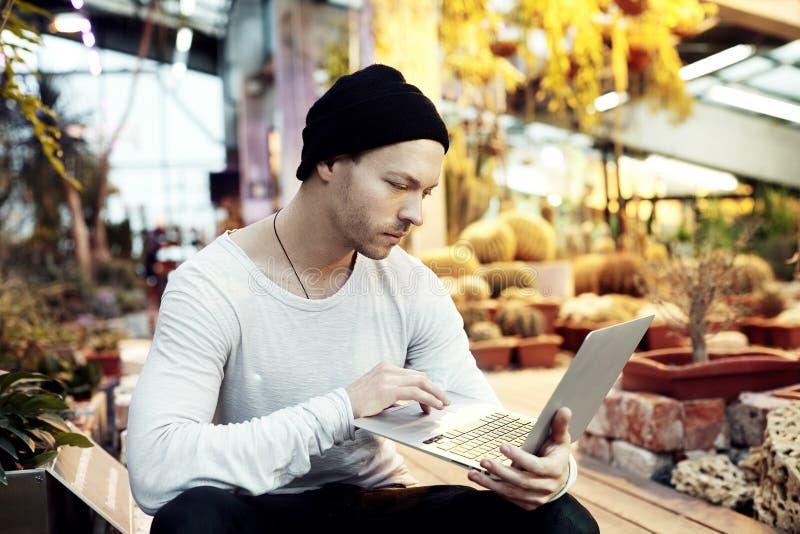 Όμορφο πορτρέτο ατόμων hipster που λειτουργεί στο πρόγραμμα ξεκινήματος για το φορητό φορητό προσωπικό υπολογιστή στοκ εικόνες