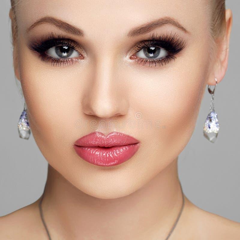 Όμορφο πορτρέτο γυναικών που απομονώνεται στο γκρίζο υπόβαθρο Νέα γυναίκα με τα πλήρη χείλια, μακροχρόνια eyelashes, σαφές δέρμα, στοκ εικόνα