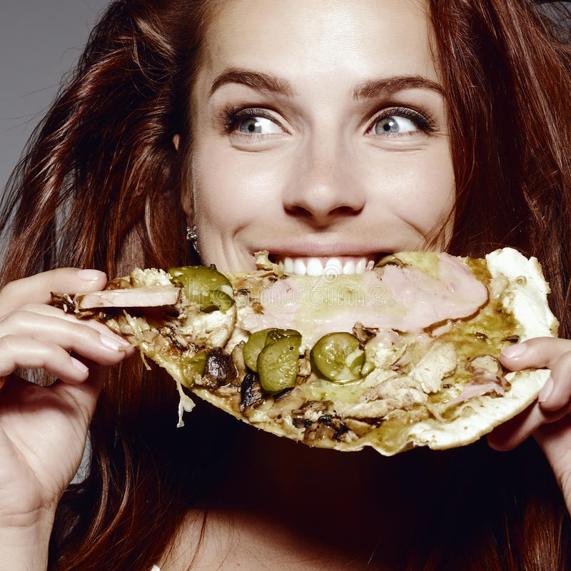 Όμορφο πορτρέτο κινηματογραφήσεων σε πρώτο πλάνο της νέας γυναίκας που τρώει την πίτσα στοκ εικόνες