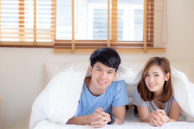 Όμορφο πορτραίτο νεαρό ασιατικό ζευγάρι χαλαρώνει και ικανοποιείται μαζί στην κρεβατοκάμαρα στο σπίτι στοκ φωτογραφία