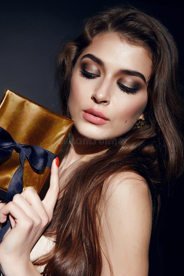 Όμορφο προκλητικό βράδυ γυναικών brunett makeup με το κιβώτιο παρόν στοκ φωτογραφία