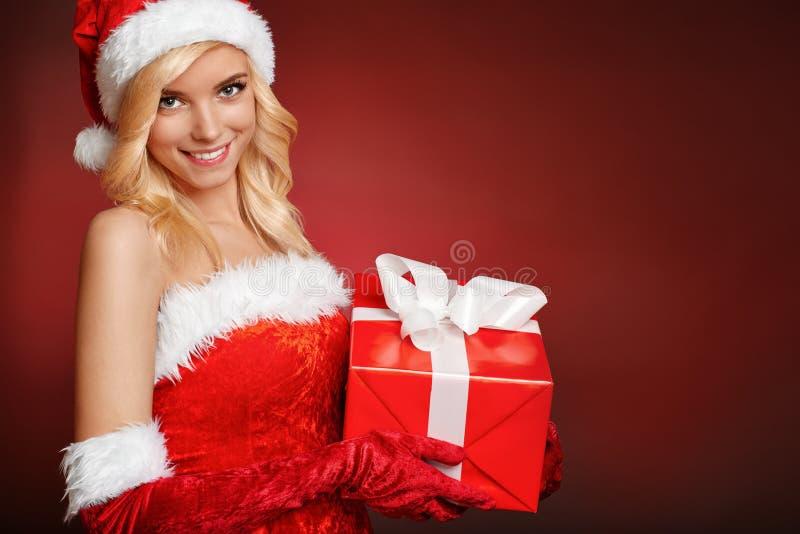 Όμορφο προκλητικό κορίτσι Άγιου Βασίλη με το κιβώτιο δώρων. στοκ εικόνα