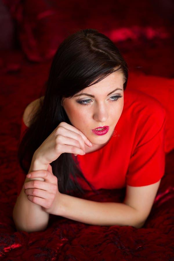 Όμορφο προκλητικό κορίτσι που στηρίζεται στο κρεβάτι στοκ φωτογραφίες