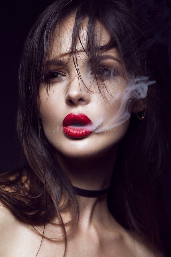 Όμορφο προκλητικό κορίτσι brunette με το φωτεινό makeup, κόκκινα χείλια, καπνός από το στόμα Πρόσωπο ομορφιάς στοκ φωτογραφία με δικαίωμα ελεύθερης χρήσης