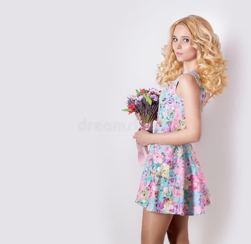 Όμορφο προκλητικό μέτριο γλυκό τρυφερό κορίτσι με τα σγουρά ξανθά μαλλιά που στέκονται στο άσπρο υπόβαθρο με μια ανθοδέσμη των λο στοκ εικόνες