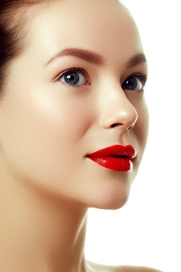 Όμορφο πρόσωπο αγνότητας γυναικών ` s με το φωτεινό κόκκινο χείλι makeup στοκ εικόνες