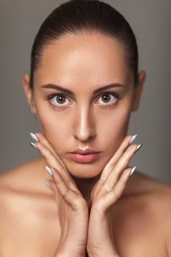 Όμορφο πρόσωπο αφής γυναικών πρότυπο με την ελαφριά nude σύνθεση στοκ φωτογραφία με δικαίωμα ελεύθερης χρήσης