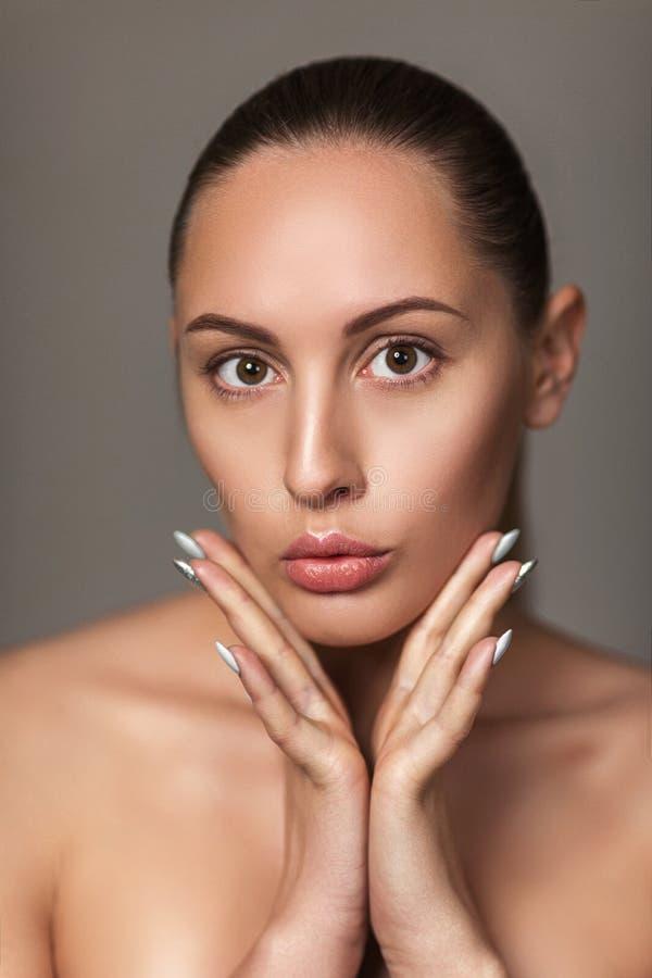 Όμορφο πρόσωπο αφής γυναικών πρότυπο με την ελαφριά nude σύνθεση στοκ εικόνα