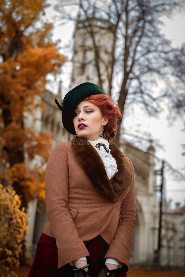 Όμορφο πρόσωπο γυναικών στο καπέλο και τα κόκκινα δέντρα φθινοπώρου τρίχας στοκ φωτογραφία με δικαίωμα ελεύθερης χρήσης