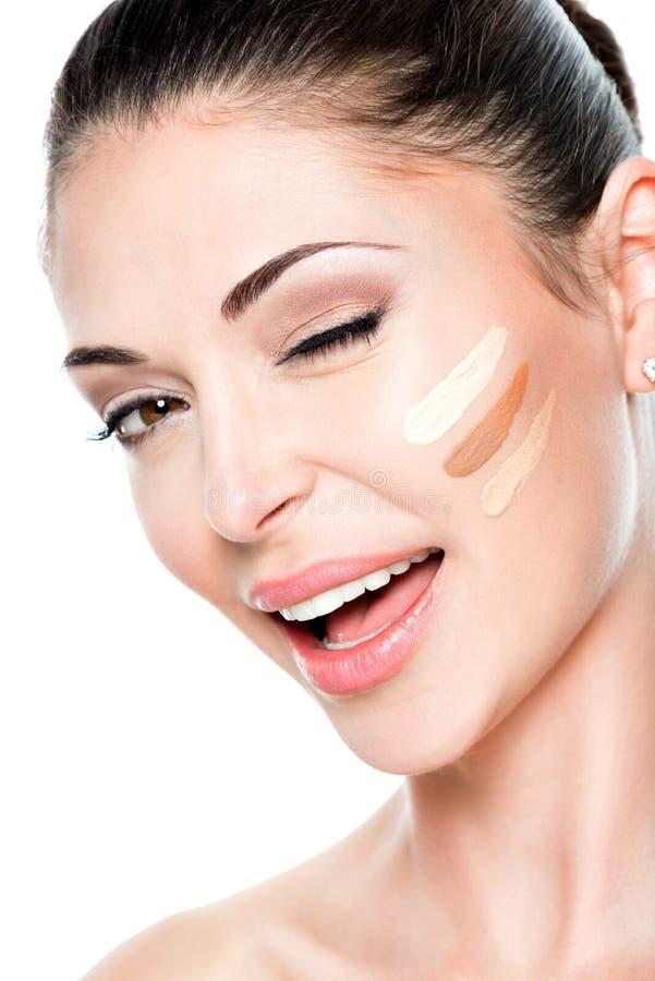 Όμορφο πρόσωπο της γυναίκας με το καλλυντικό ίδρυμα σε ένα δέρμα. στοκ εικόνες