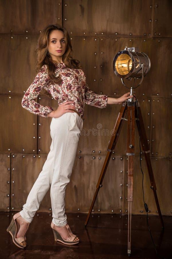 Όμορφο πρότυπο κοριτσιών brunette στο άσπρο παντελόνι που θέτει κοντά στον τοίχο μετάλλων και έναν εκλεκτής ποιότητας λαμπτήρα στοκ φωτογραφία