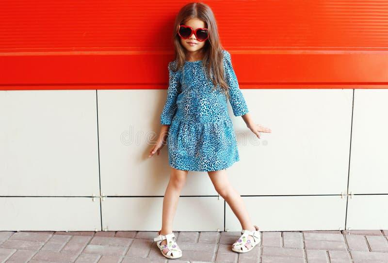 Όμορφο πρότυπο μικρών κοριτσιών που φορά ένα φόρεμα και τα γυαλιά ηλίου λεοπαρδάλεων πέρα από το ζωηρόχρωμο κόκκινο στοκ εικόνες