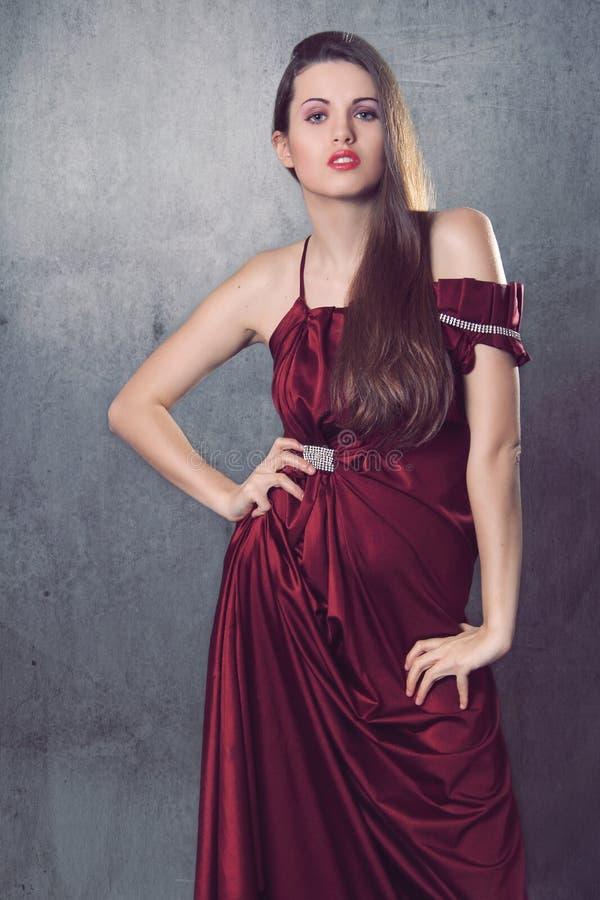 Όμορφο πρότυπο μόδας στο κομψό κόκκινο φόρεμα στοκ εικόνα