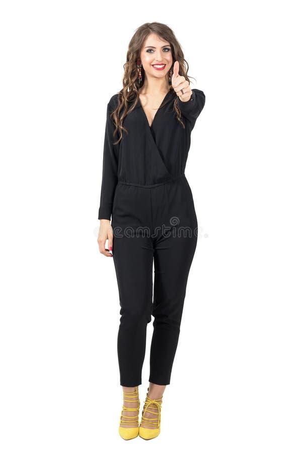 Όμορφο πρότυπο μόδας στο μαύρο jumpsuit με τον αντίχειρα επάνω στη χειρονομία στοκ φωτογραφία με δικαίωμα ελεύθερης χρήσης