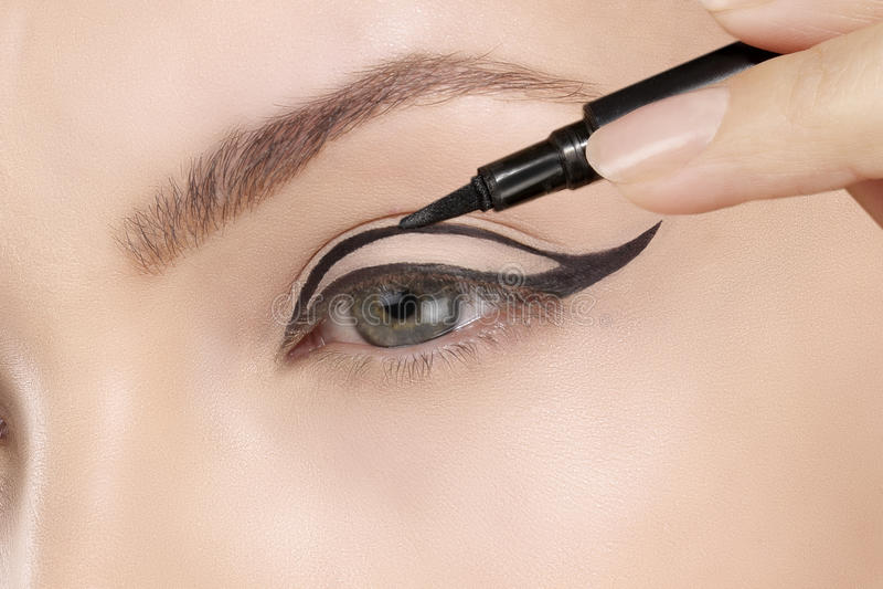 Όμορφο πρότυπο που εφαρμόζει eyeliner την κινηματογράφηση σε πρώτο πλάνο στο μάτι στοκ εικόνα