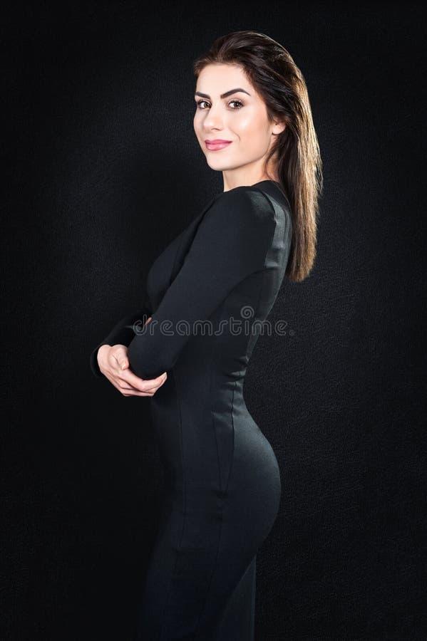 Όμορφο πρότυπο χαμόγελου, επιχειρησιακή γυναίκα που στέκεται στο μαύρο κλίμα στοκ εικόνες με δικαίωμα ελεύθερης χρήσης