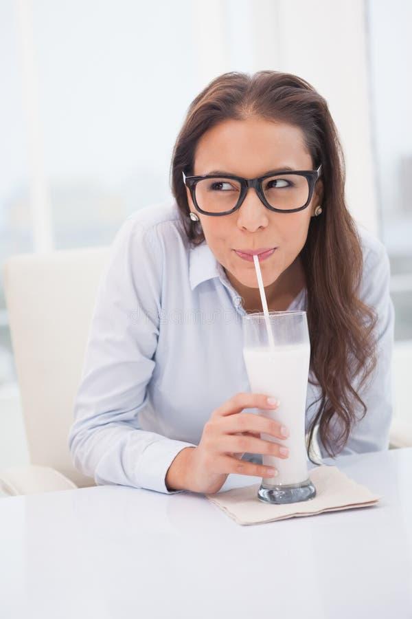 Όμορφο πόσιμο γάλα επιχειρηματιών στο γραφείο της στοκ εικόνα
