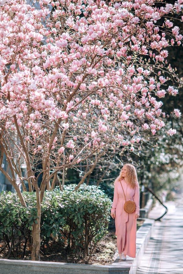 Όμορφο ρομαντικό κορίτσι άνοιξη στο φόρεμα μόδας που στέκεται στα ανθίζοντας δέντρα magnolia στοκ εικόνα με δικαίωμα ελεύθερης χρήσης