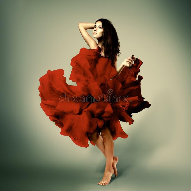 Όμορφο ρομαντικό κορίτσι στο κόκκινο φόρεμα λουλουδιών με τη μακριά τρίχα broun στοκ φωτογραφία