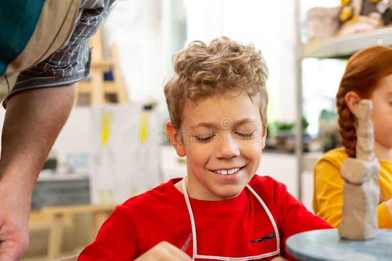 Όμορφο σγουρό αγόρι που χαμογελά αισθαμένος καλός στο σχολείο τέχνης στοκ φωτογραφία με δικαίωμα ελεύθερης χρήσης