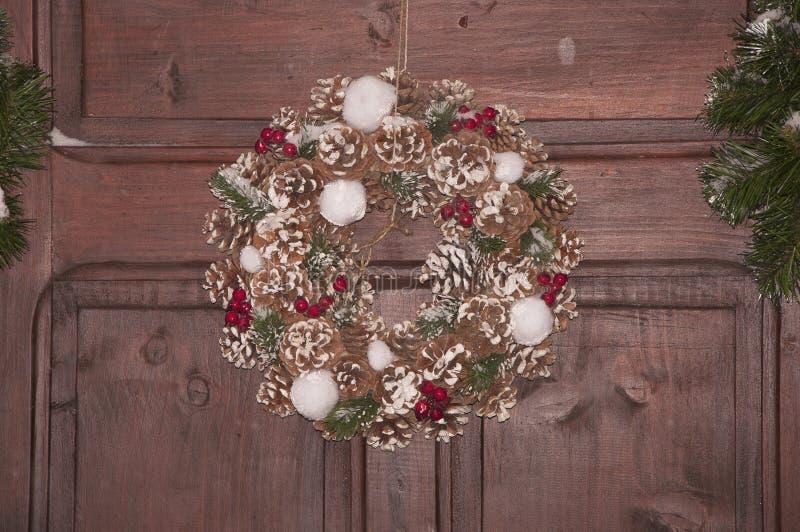 Όμορφο στεφάνι Χριστουγέννων με το πράσινους κωνοφόρο, τους κώνους και τα μούρα Νέα διακόσμηση έτους στο καφετί υπόβαθρο στοκ εικόνα