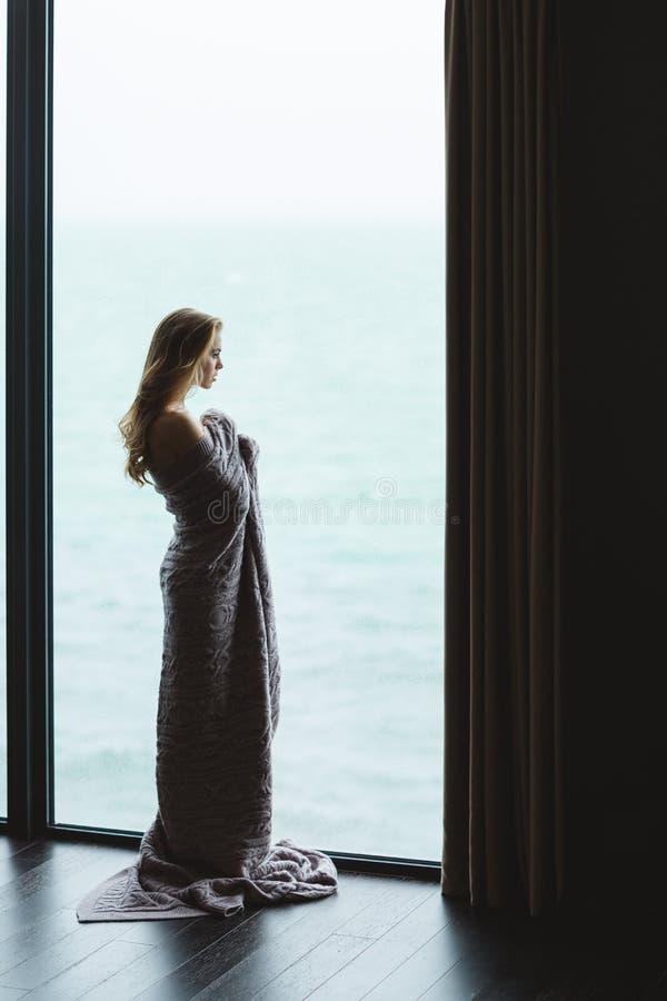 Όμορφο στοχαστικό θηλυκό με τη μακρυμάλλη στάση στο πλεκτό coverlet στοκ φωτογραφίες