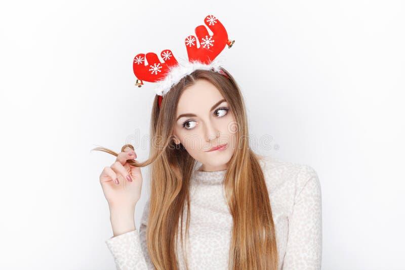 Όμορφο συναισθηματικό ξανθό θηλυκό πρότυπο headpiece ελαφιών santa ένδυσης οι χαιρετισμοί έννοιας Χριστουγέννων ανασκόπησης απομό στοκ φωτογραφία
