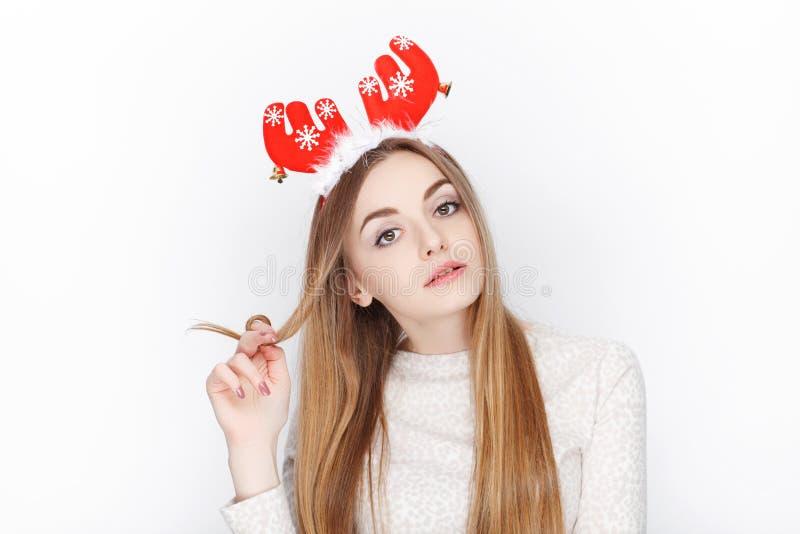 Όμορφο συναισθηματικό ξανθό θηλυκό πρότυπο headpiece ελαφιών santa ένδυσης οι χαιρετισμοί έννοιας Χριστουγέννων ανασκόπησης απομό στοκ εικόνα