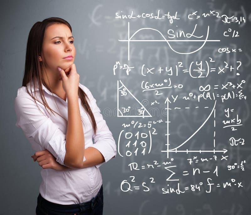 Όμορφο σχολικό κορίτσι που σκέφτεται για τα σύνθετα μαθηματικά σημάδια στοκ φωτογραφία