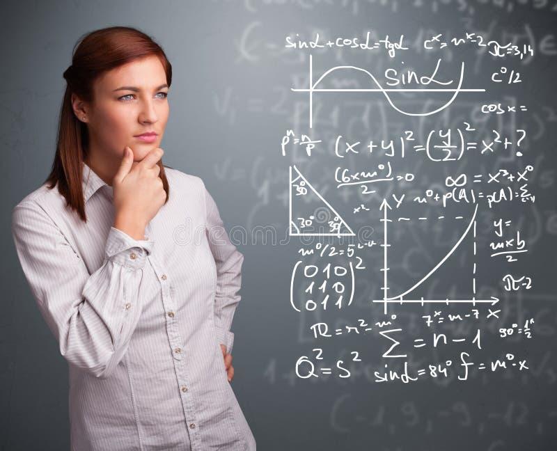 Όμορφο σχολικό κορίτσι που σκέφτεται για τα σύνθετα μαθηματικά σημάδια στοκ εικόνες