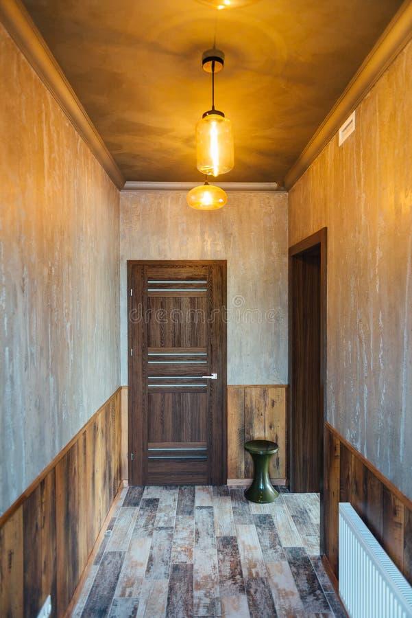 Όμορφο σύγχρονο ντεκόρ καθιστικών με την ξύλινη πόρτα και το γκρίζο υπόβαθρο κουρτινών στοκ εικόνες