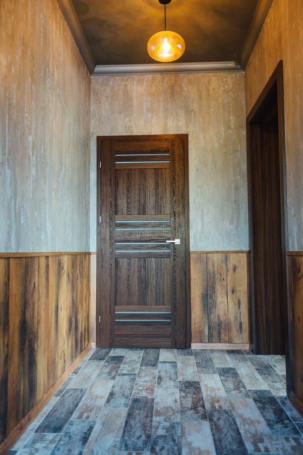 Όμορφο σύγχρονο ντεκόρ καθιστικών με την ξύλινη πόρτα και το γκρίζο υπόβαθρο κουρτινών στοκ εικόνες με δικαίωμα ελεύθερης χρήσης