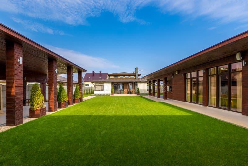 Όμορφο σύγχρονο ξύλινο σπίτι με τα λεκιασμένα παράθυρα γυαλιού, άποψη στοκ εικόνα με δικαίωμα ελεύθερης χρήσης