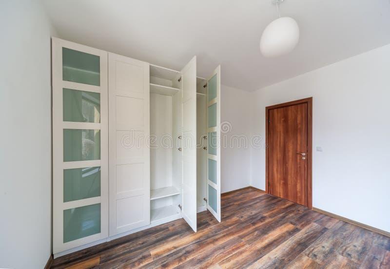 Όμορφο σύγχρονο σπίτι, κενό δωμάτιο με το άσπρο ντουλάπι ντουλαπών, ξύλινο πάτωμα στοκ εικόνες με δικαίωμα ελεύθερης χρήσης