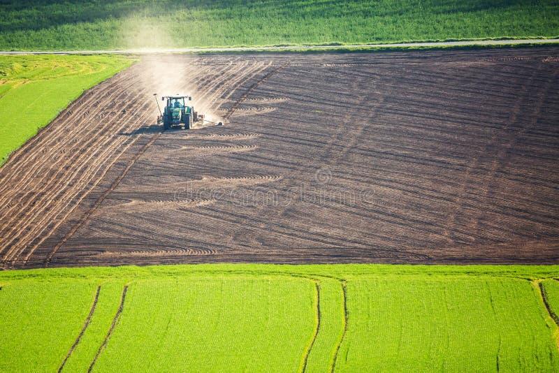 Όμορφο τοπίο άνοιξη με το λειτουργώντας τρακτέρ στον πράσινο και καφετή τομέα στη νότια Μοραβία, Δημοκρατία της Τσεχίας γεωργία c στοκ εικόνες