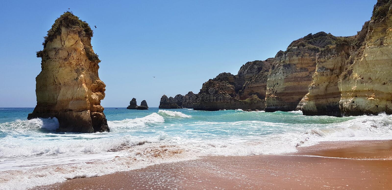Όμορφο τοπίο: απότομοι βράχοι στον τυρκουάζ Ατλαντικό Ωκεανό κοντά στην παραλία Praia Dona Ana, Λάγκος, Πορτογαλία στοκ φωτογραφίες