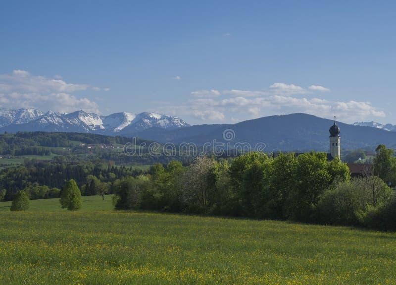 Όμορφο τοπίο βουνών άνοιξη αγροτικό στις βαυαρικές Άλπεις με το χωριό εκκλησιών και τις χιονισμένες αιχμές βουνών στοκ φωτογραφίες με δικαίωμα ελεύθερης χρήσης