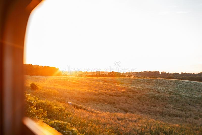 Όμορφο τοπίο με ένα φωτεινό πορτοκαλί ηλιοβασίλεμα και πράσινος τομέας έξω από το παράθυρο τραίνων Ταξίδι με το τραίνο στο ηλιοβα στοκ φωτογραφία με δικαίωμα ελεύθερης χρήσης