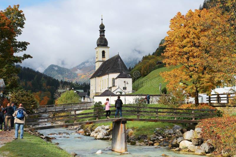 Όμορφο τοπίο μιας ξύλινης γέφυρας πέρα από ένα ρεύμα μπροστά από μια εκκλησία με τα ομιχλώδη βουνά στο υπόβαθρο στοκ φωτογραφίες