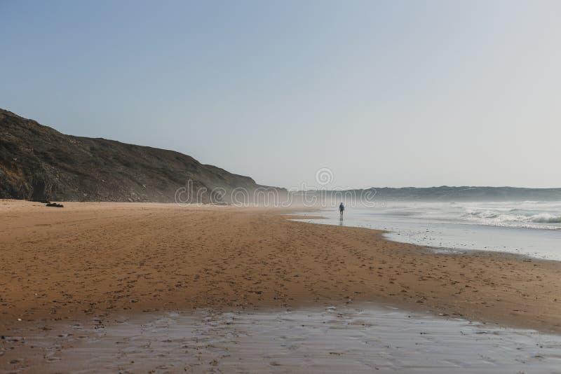 όμορφο τοπίο στο ηλιοβασίλεμα στην Πορτογαλία, παραλία Bordeira με ένα πρόσωπο που περπατά από την ακροθαλασσιά καλοκαίρι και ένν στοκ εικόνα με δικαίωμα ελεύθερης χρήσης